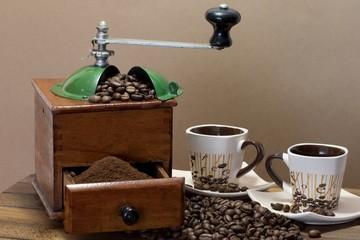 Molinillo de café con granos de café esparcidos y tazas