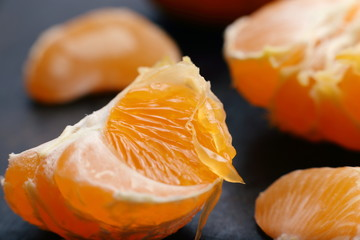 Cantels of mandarins with peels on a dark table. Macro