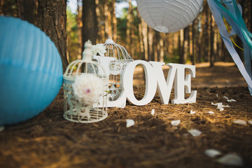 Beautiful place for outside wedding ceremony in wood. Wedding settings. Love - wooden inscription. Festive stylish decor made by blue and white Japanese lanterns and many ribbons. Horizontal image.