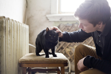 Caucasian man petting cat in living room