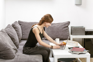 girl holding a credit card and enters data into a laptop sitting