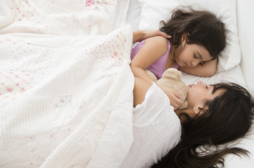 Hispanic mother and daughter sleeping in bed