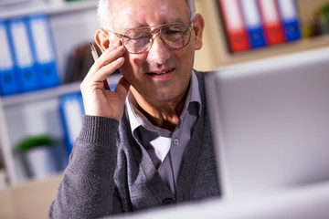 Portrait of experienced senior businessman working on laptop in his office.