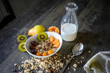 Müsli mit Früchten zum Frühstück auf altem Holztisch