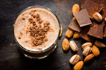 coffee chocolate smoothie on a dark background with chocolate and nuts. Selective focus. Milkshake. Protein diet. Healthy food concept.