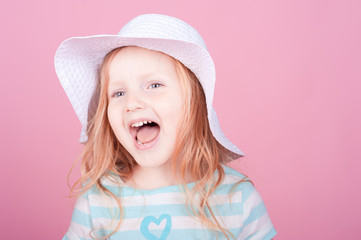 Cute little girl laughing on pink background in studio. Wearing hat. Cheerful.