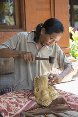 Wood worker chiseling piece in studio