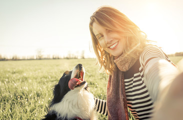 Smiling lady taking selfie with her dog
