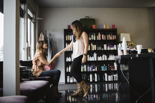 Stylist greeting client in salon