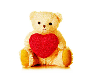 Teddy bear holding red heart Isolated on white.