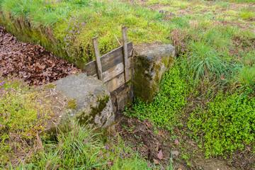 Chiusa in cemento  con saracinesca in legno in un fossato per regolare il corso dei flussi  d'acqua  per l'irrigazione