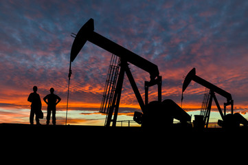 Silhouettes of Pumpjack and Oil Workers in the Oil Field