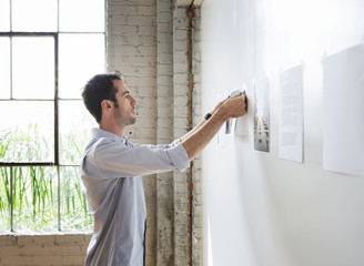 Architect hanging photos in office