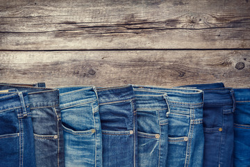 Fashion different jeans on wooden background. Retro toned. Wall mural