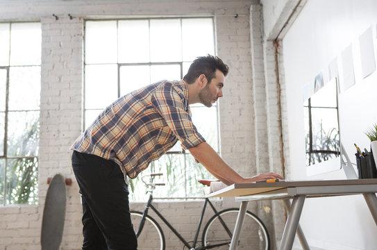Caucasian architect reading blueprints in office