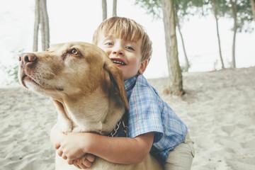 Boy hugging dog on wooded beach