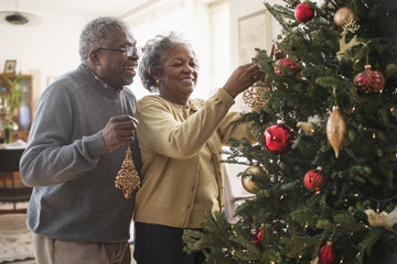 Older couple decorating Christmas tree