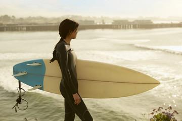 Asian surfer overlooking ocean
