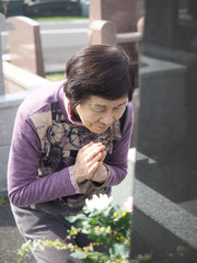 お彼岸にお墓で手を合わせる80歳の母