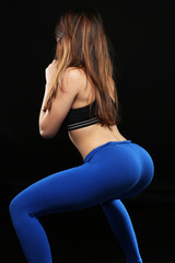 young caucasian woman doing squat on black background