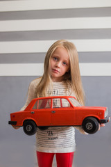 Портрет красивой девочки с большой красной машиной