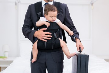 Midsection of father carrying baby while holding briefcase