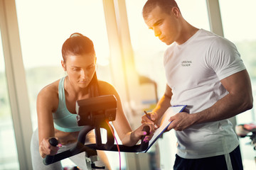 Personal trainers in the gym giving instruction and help to attr