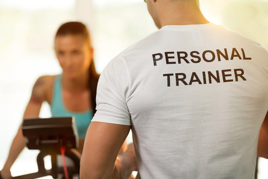 Personal trainer with woman on cycling machine at the gym