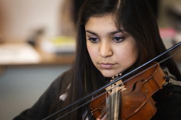 Hispanic girl playing violin in music class
