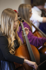 Caucasian girl playing cello in music class