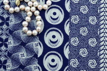 Overhead close up of pearl necklace on indigo cloth