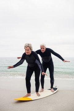 Senior couple surfing on beach