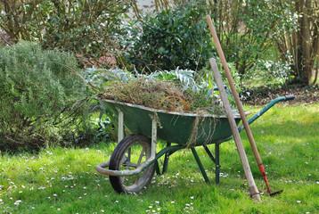 brouette dans jardin pleine de mauvaises herbes