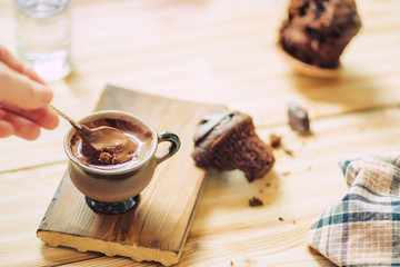 cup of hot chocolate and a chocolate muffin