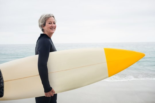 Senior woman in wetsuit holding a surfboard on the beach