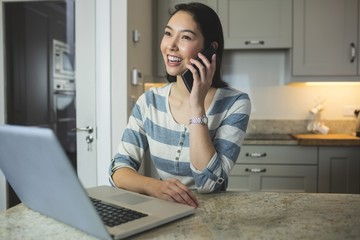 Happy woman using laptop while on call