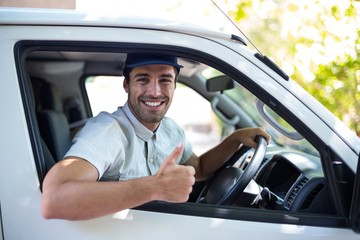 Cheerful delivery man showing thumbs up