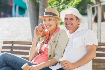 Couple looking away while sitting on bench