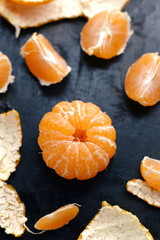 Cantels of mandarins with peels on a dark table