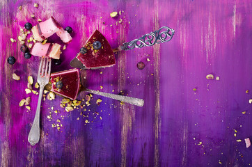 Piece of delicious raspberry cake with fresh raspberries, blueberry, currants and pistachios on shovel, bright purple, violet background. Free space for your text.
