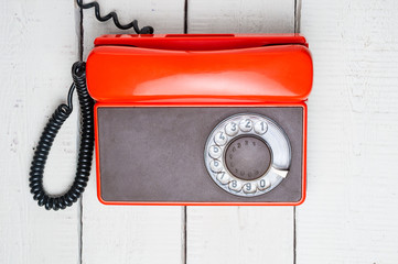 Old rotary telephone on wooden background. Top view