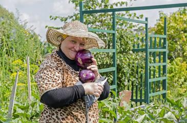 Женщина на даче радуется урожаю баклажан.
