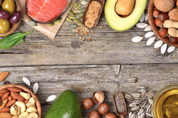 Selection of healthy fat sources on wooden table. Copyspace background. Top view.