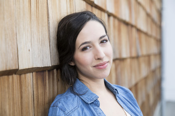 Portrait of young creative business woman in front of wood shingle panelling