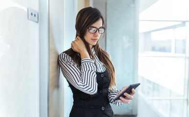 Young businesswoman looking at her smartphone