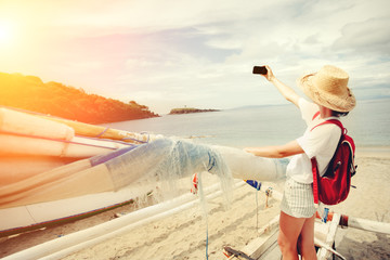Young cheerful woman taking photo with mobile phone on beautiful island (intentional sun glare and vintage color)