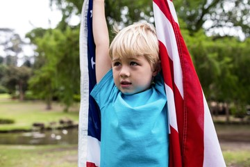 Boy holding an american flag in the park