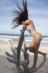 Beautiful lady standing on broken tree swaying her hair