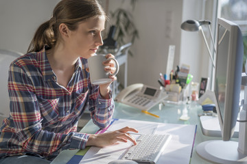 Young woman at desk in office holding cup of coffee