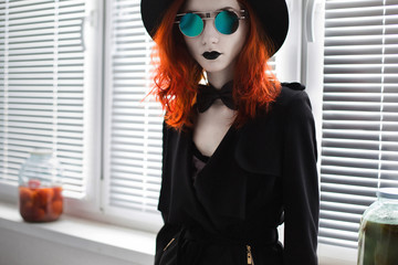 Portrait of red-haired girl in bow tie on a dark background, gothic style girl in black clothes, style fashion, black lips, a girl standing, round glasses and a hat, blinds on the balcony